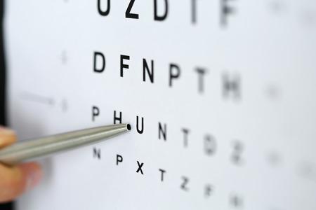 시력 검사 테이블에 편지를 가리키는 실버 볼펜. 시력 검사 및 교정, 우수한 시력 교정 또는 안경점, 레이저 수술 대안, 운전자 건강 진단 검사 개념