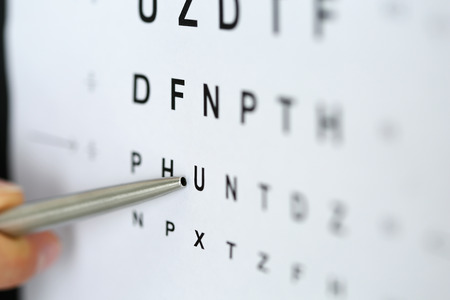 shortsightedness: Silver ballpoint pen pointing to letter in eyesight check table. Sight test and correction, excellent vision or optician shop, laser surgery alternative, driver health certificate examination concept