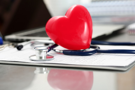 pacemaker: Medical stethoscope head and red toy heart lying on cardiogram chart closeup. Cardio therapeutist, physician make cardiac physical, heart rate measure, arrhythmia, resuscitation and pacemaker concept