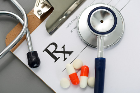 pharmacologist: Prescription lying on clipboard pad with stethoscope and pile of pills. Panacea and patient life save, legal drug store, prescribe treatment, contraception concept. Empty form ready to be used Stock Photo