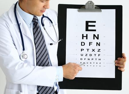 oculista: Doctor de la medicina detiene el filtro grande portapapeles con tabla de verificación de la vista y el punto con el bolígrafo pluma de plata a la misma. Excelente visión alternativa de la cirugía con láser, conductor certificado concepto de examen