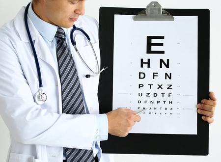 oculist: Medicine doctor hold big clipboard pad with eyesight check table and point with silver ballpoint pen to it. Excellent vision, laser surgery alternative, driver certificate examination concept Stock Photo