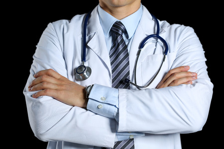 lifestyle disease: Male medicine therapeutist doctor hands crossed on his chest hold stethoscope isolated on black. Physical and disease prevention, examine patient, 911, instrument shop, healthy lifestyle concept
