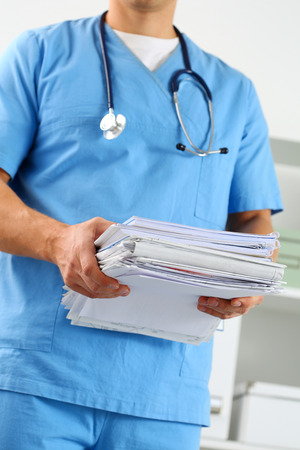 therapeutist: Hands of medicine therapeutist doctor wearing blue uniform holding pile of business papers at work table. Medications consumption account, bureaucracy in hospital work, patient documentation concept