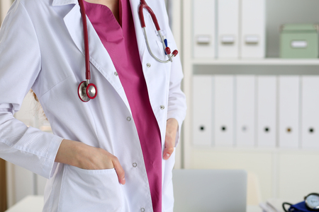 er: Stethoscope lying on female therapeutist doctor chest in office. Medic store, physical and patient disease prevention, er consultant body, 911, profession, pulse measure, healthy lifestyle concept Stock Photo