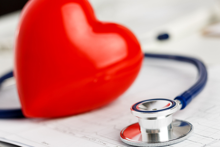 er: Medical stethoscope head and red toy heart lying on cardiogram chart closeup. Cardio therapeutist, pulse graph, cardiac physical, heart rate measure, arrhythmia, 911, er and resuscitation concept Stock Photo