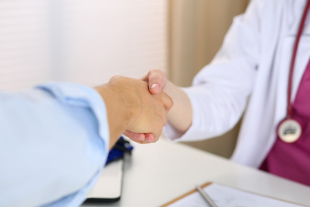 visitador medico: Female medicine doctor shake hand as hello with male patient in office closeup. Welcoming friend, introduction or thanks gesture. Tests advertisement concept. Physician ready to examine patient