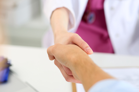 handclasp: Female medicine doctor shake hand as hello with male patient in office closeup. Welcoming friend, introduction or thanks gesture. Tests advertisement concept. Physician ready to examine patient