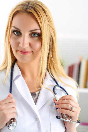 er: Beautiful smiling female doctor stand in office holding stethoscope portrait. Physical, exam, er, disease prevention, ward round, patient visit check, 911, prescribe remedy, healthy lifestyle concept