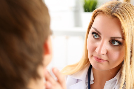 Belle médecin de médecine féminine avec seus face à examiner le patient. Les soins médicaux, maladie diagnostic, consultation physique médecin, le concept d'assurance. Dermatologue ou d'examen oncologue