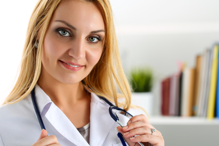 prescribe: Beautiful smiling female doctor stand in office holding stethoscope portrait. Physical, exam, er, disease prevention, ward round, patient visit check, 911, prescribe remedy, healthy lifestyle concept