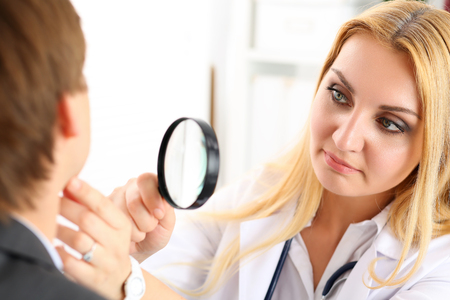 oncologist: Beautiful female medicine doctor with serious face examine patient. Medical care, illness diagnosing, physical, physician consultation, insurance concept. Dermatologist or oncologist examination Stock Photo