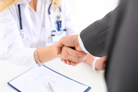 visitador medico: Female medicine doctor shake hand as hello with male businessman in office closeup. Welcoming friend, introduction or thanks gesture. Tests advertisement concept. Physician ready to examine patient Foto de archivo
