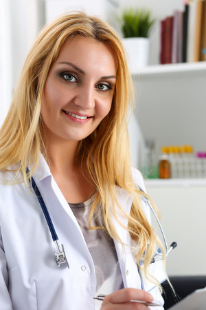 lifestyle disease: Beautiful smiling female doctor hold clipboard pad writing something. Physical, exam, er, disease prevention, ward round, patient visit check, 911, prescribe remedy, healthy lifestyle concept