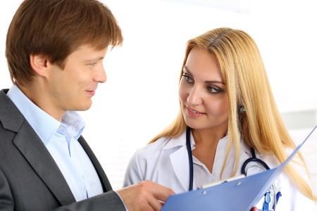 Smiling beautiful female medicine doctor explain diagnosis to male patient in business suit holding and showing pad. Physical, disease prevention, 911, prescribe remedy, healthy lifestyle concept