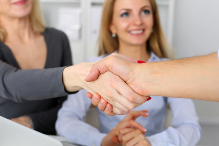 shakes hands: Business people shake hands as hello in office closeup. Friend welcome, introduction, greet or thanks gesture, product advertisement, partnership approval, arm, strike a bargain on deal concept