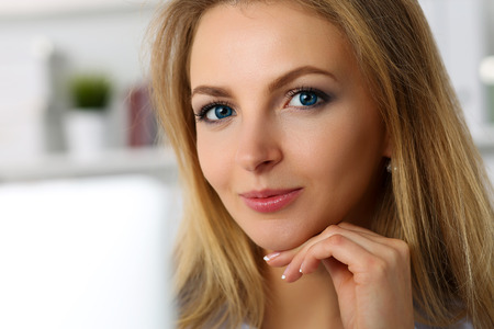 ip camera: Beautiful blonde smiling businesswoman work with laptop computer looking in camera portrait. White collar worker at workplace, job offer, internet web chat, wireless ip telephony, social net concept Stock Photo