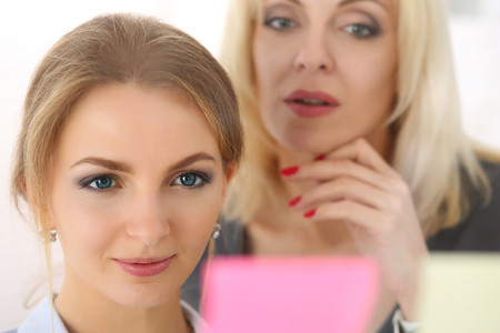 sticky: Two beautiful smiling businesswoman make some marks on sticky notes on glass wall. Fresh view, discuss problem, review situation, look at new angle, professional training, memo graph or chart concept Stock Photo