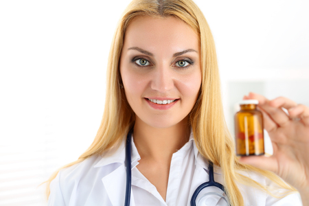 pharmacologist: Beautiful smiling female medicine doctor hold and give to patient jar of pills. Disease prevention, er, 911, healthy life style, therapeutist examination, heart heal, legal narcotic store concept
