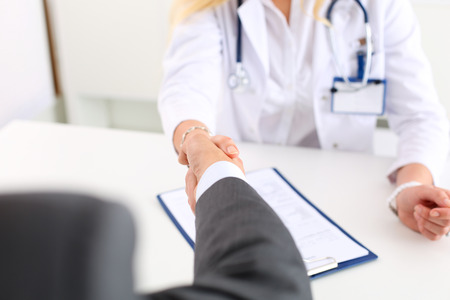 meet and greet: Female medicine doctor shake hand as hello with male businessman in office closeup. Welcoming friend, introduction or thanks gesture. Tests advertisement concept. Physician ready to examine patient Stock Photo