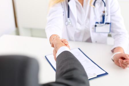 visitador medico: Mujer médico de medicina movimiento de la mano como saludo con el empresario masculina en primer plano oficina. amigo de bienvenida, introducción o gesto de agradecimiento. Pruebas de publicidad concepto. Médico dispuesto a examinar paciente