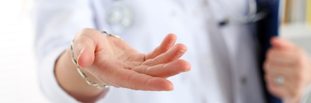 Female medicine doctor offering helping hand closeup. Friendly and cheerful gesture. Life choice, tests advertisement, 911, cancer, incurable illness concept. Physician ready examine and save patient