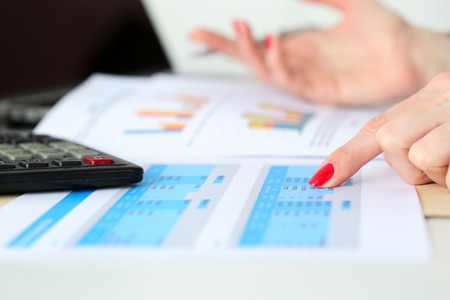 Hand of businesswoman point finger to financial table checking balance closeup. Internal Revenue Service inspector check statistics, investment audit, earnings, savings, loan and credit concept
