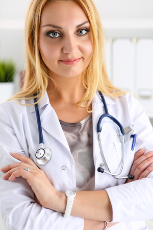 Beautiful smiling female doctor with hands crossed on chest portrait. Medic store, physical and patient disease prevention, er consultant, 911, profession, pulse measure, healthy lifestyle concept