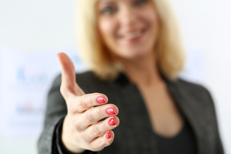 meet and greet: Businesswoman offer hand to shake as hello in office closeup. Serious business, friendly support service, excellent prospect, introduction or thanks gesture, gratitude, invite to participate concept