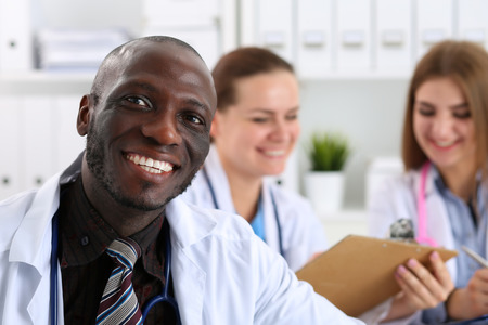 disease prevention: Portrait of young handsome black male doctor with colleagues working in background. Good news, excellent patient history, therapeutist prescribe remedy, physical, 911, disease prevention concept