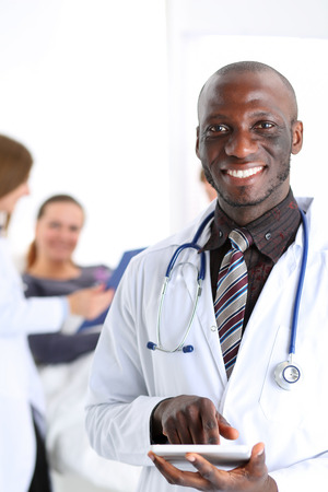 physician: Black male doctor point with finger in digital tablet pc touch screen portrait with patient lying in bad in background. Professional equipment, therapeutist ward round, search opportunities concept Stock Photo