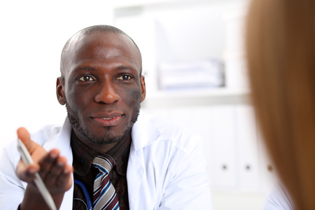 communicate concept: Black skinned male doctor communicate with patient. Physical exam, cheerful therapeutist and client, disease prevention, ward round, good news report, 911, prescribe remedy, healthy lifestyle concept