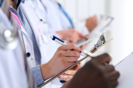 Group of doctors hold pens and clipboard pads make some notes during medical conference. Therapeutist seminar, professional dispute, hospital life, new remedy or worker introducing concept Stock Photo