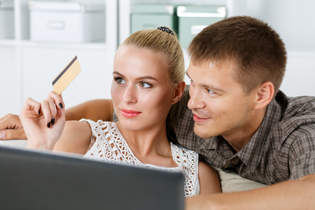 over paying: Family couple make shopping over internet paying with golden credit card. Husband and wife buy new stuff in house. Banking technology, electronic store, comfort and time saving concept Stock Photo