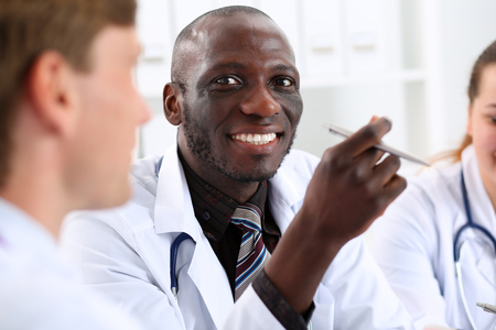 Portrait of young handsome black male doctor with colleagues working in background. Good news, excellent patient history, therapeutist prescribe remedy, physical, 911, disease prevention concept photo