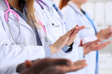 introducing: Group of doctors clapping their hands during medical conference. Therapeutist seminar, professional dispute, hospital life, new remedy or worker introducing, colleague happy birthday concept Stock Photo