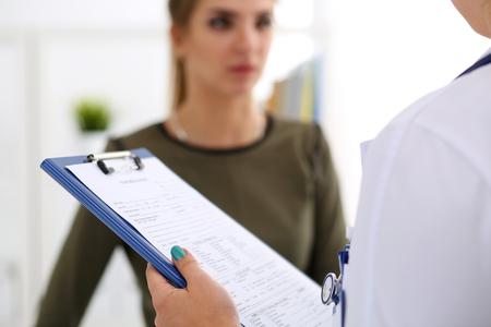 Female doctor hand holding and filling patient history list at clipboard pad during physical. Exam, er, disease prevention, ward round, visit check, 911, prescribe remedy, healthy lifestyle concept