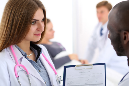 Two doctors share and discuss important document on clipboard pad. Human interaction, professional dispute, therapeutist prescribe remedy, physical, illness prevention, 911, healthy lifestyle concept photo