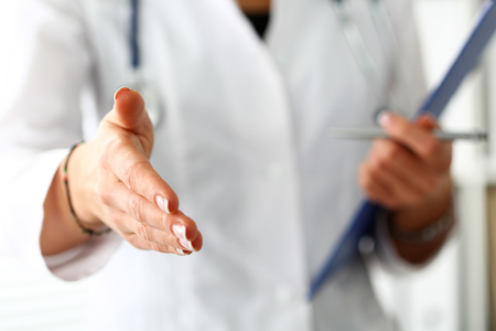 healthcare visitor: Female medicine doctor offering hand to shake in office closeup. Greeting and welcoming friend, introduction or thanks gesture. Tests advertisement concept. Physician ready to examine patient Stock Photo