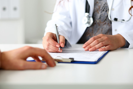 Female doctor hand hold silver pen filling patient history list at clipboard pad. Physical, exam, er, disease prevention, ward round, visit check, 911, prescribe remedy, healthy lifestyle concept