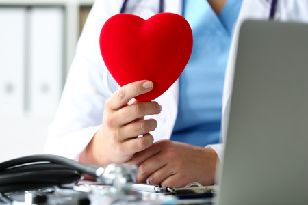Female medicine doctor hold in hands red toy heart in front of her chest. Cardio therapeutist, student education, physician make cardiac physical, heart rate measure, arrhythmia concept Stock Photo
