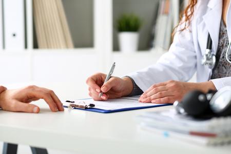Femminile penna d'argento della stretta della mano medico riempimento lista storia del paziente al pad appunti. Fisica, esame, ehm, la prevenzione delle malattie, reparto rotondo, visita di controllo, 911, prescrivere rimedio, stile di vita sano concetto