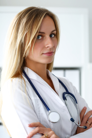 stethoscope: Beautiful smiling female doctor with hands crossed on chest portrait. Medic store, physical and patient disease prevention, er consultant, 911, profession, pulse measure, healthy lifestyle concept