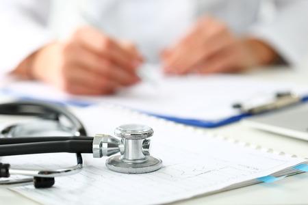 Medische stethoscoop die op de close-up van de cardiogramgrafiek ligt terwijl geneeskunde arts die op achtergrond werkt. Cardiologiezorg, gezondheid, bescherming, preventie en hulp. Gezond leven of verzekering concept