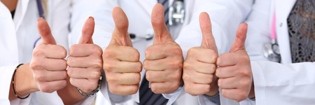 Three doctors show OK sign with thumb up in row. High level service, best treatment, 911, healthy lifestyle, satisfied patient, therapeutist consultation work, physical concept. Letterbox view