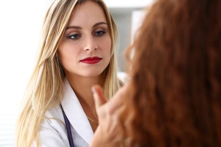 Belle femme médecin avec un visage sérieux examiner le patient. Soins médicaux, diagnostic de maladie, consultation physique, médecin, concept d'assurance. Dermatologue ou examen d'oncologue