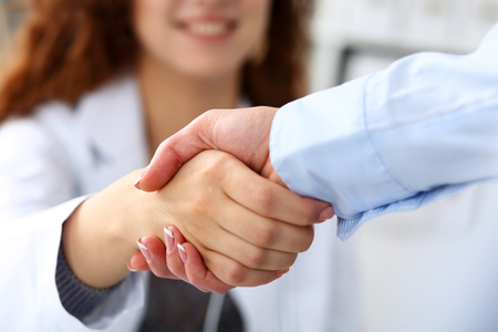 여성 의사 의사 사무실 근접 촬영에서 사업가로 안락 함께 악수. 환영하는 친구, 소개 또는 감사 제스처. 광고 개념을 테스트합니다. 환자를 검사 할 준 스톡 콘텐츠