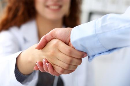Vrouwelijke geneeskunde arts schudt de hand als hallo met zakenvrouw in kantoor close-up. Verwelkomende vriend, inleiding of dankgebaar. Tests advertentie concept. Arts klaar om patiënt te onderzoeken