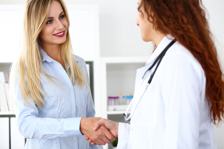 Female doctor shake hand as hello with beautiful blonde patient in office closeup. Welcoming friend, introduction or thanks gesture. Tests advertisement concept. Physician ready to examine patient Stock Photo
