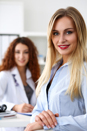 medical career: Satisfied happy beautiful smiling female patient with doctor at her office. High level and quality medical service, therapeutist consultation, work and career, physical, healthy lifestyle concept